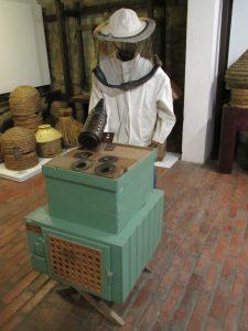 Ekspozycja kombinezonu pszczelarskiego i drewnianego ula