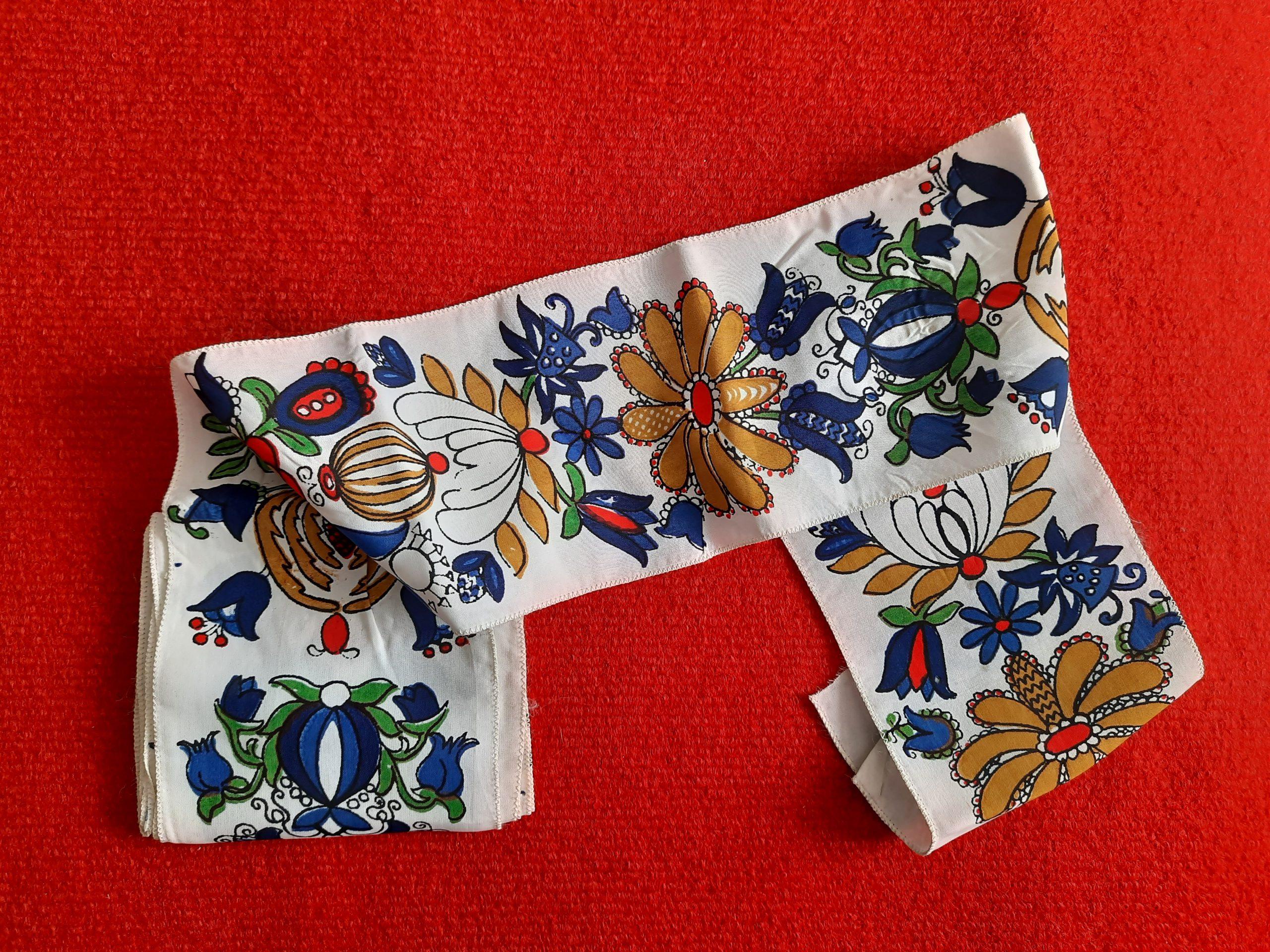 Biała szarfa z motywem haftu kaszubskiego na czerwonym tle.